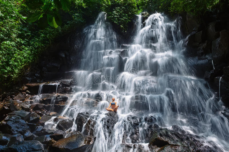 妇女坐在瑜伽姿势的岩石在小瀑布瀑布下 图库摄影