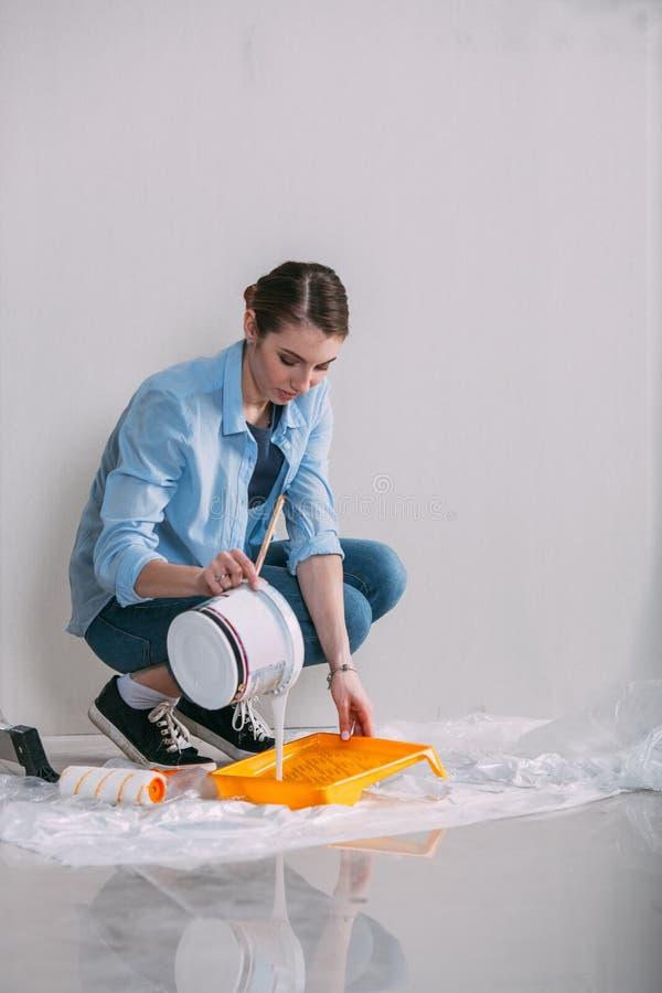 妇女坐地板和混合的墙壁油漆 库存图片