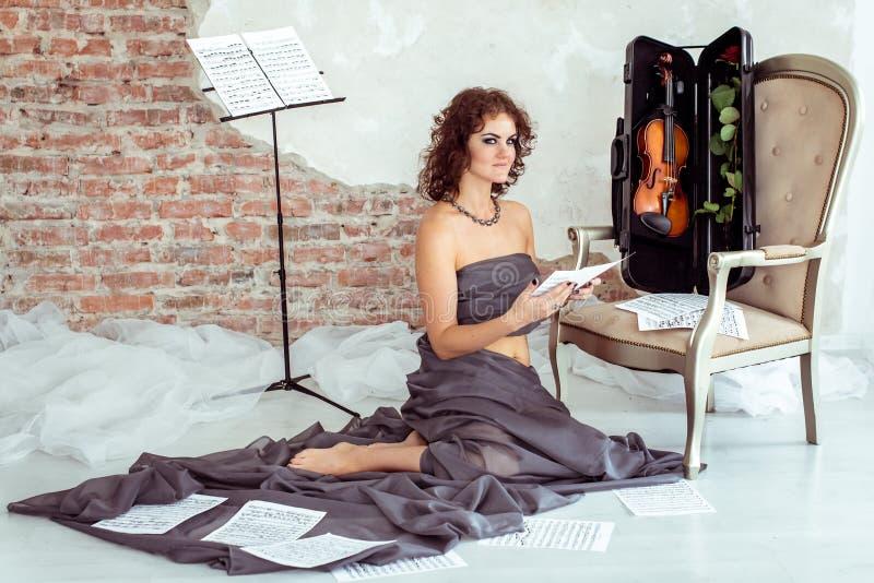 妇女坐地板在与小提琴的椅子附近 免版税图库摄影