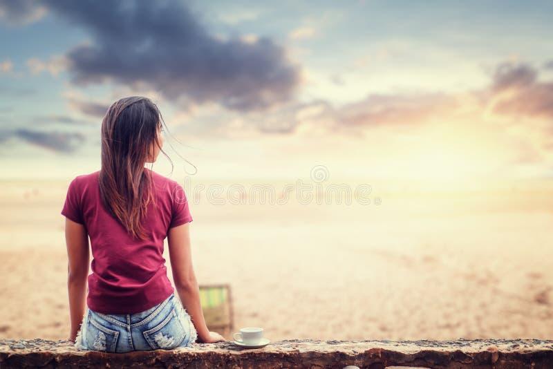 妇女坐地面在与日落时间和好的云彩的海滩附近 免版税图库摄影