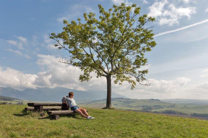 妇女坐夏天小山在Liptovsky Trnovec,斯洛伐克附近 免版税库存照片