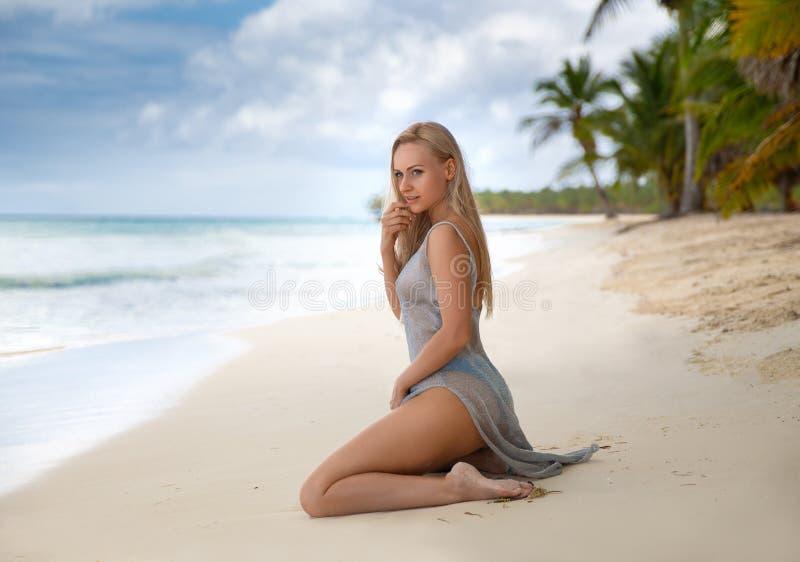 妇女坐多米尼加共和国的白色沙滩 免版税库存照片