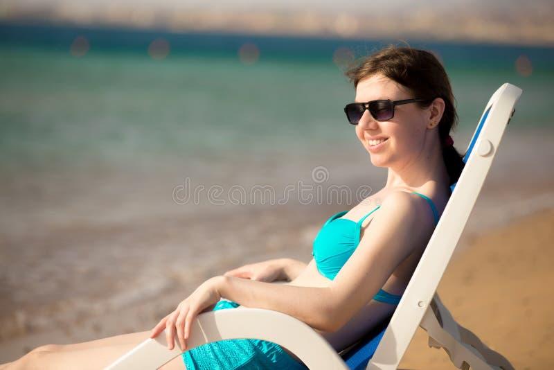 妇女坐太阳deckchair 免版税库存图片