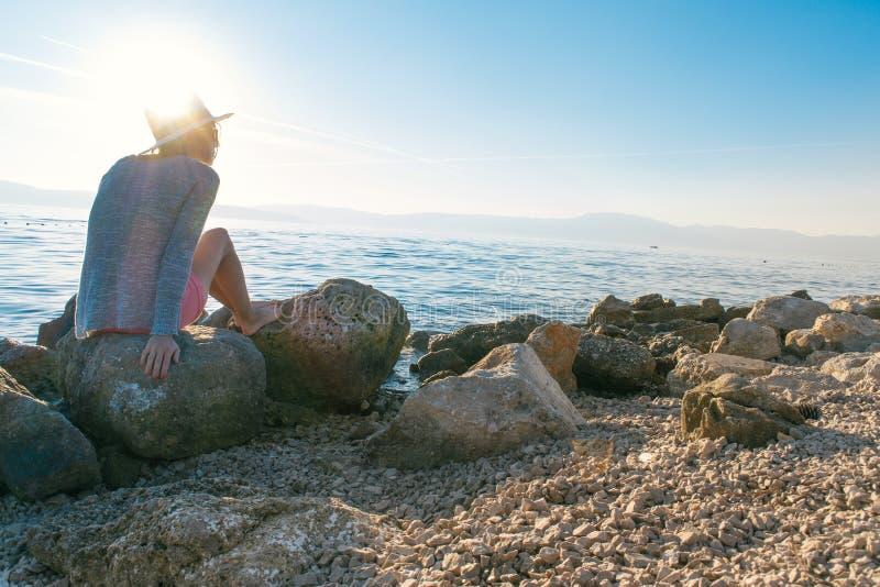 妇女坐岩石由海 免版税库存图片