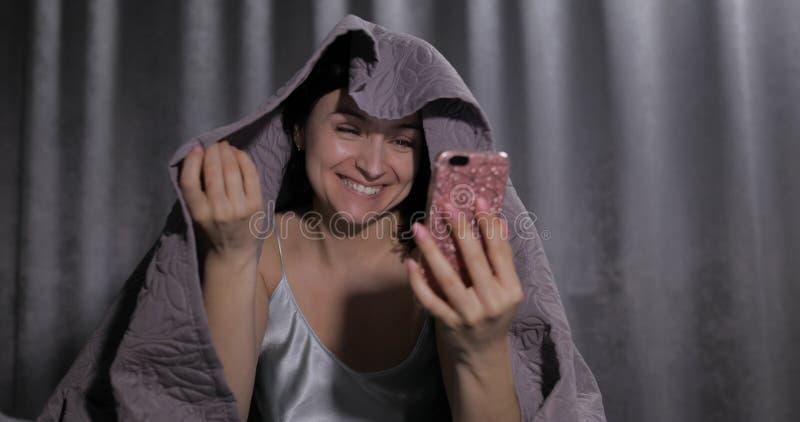 妇女坐床在毯子下 享受对朋友的视频聊天智能手机的 免版税库存照片