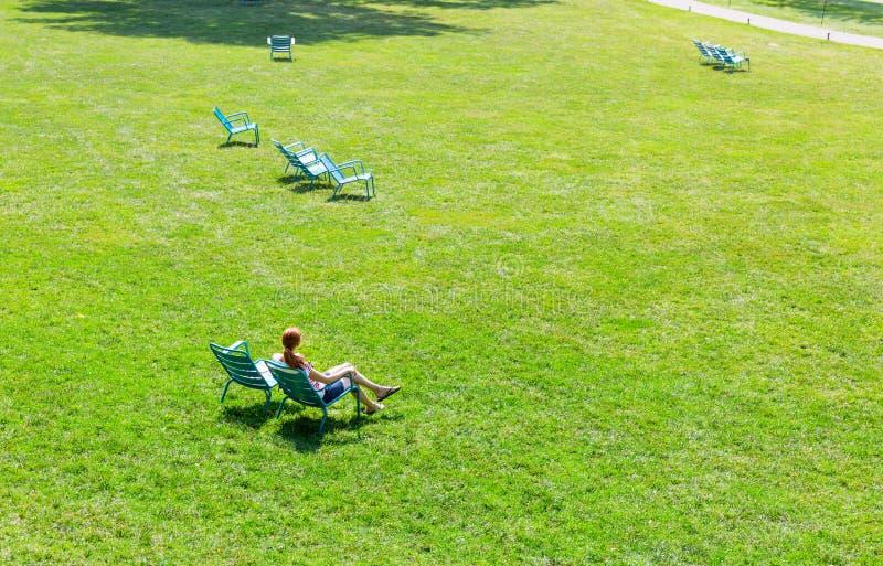 妇女坐扶手椅子在草甸中间 免版税图库摄影