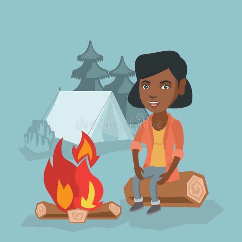 妇女坐日志在野营的营火附近 皇族释放例证