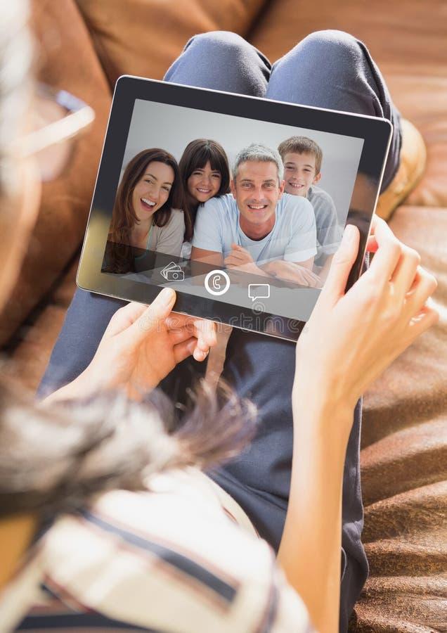 妇女坐有的沙发与家庭的录影电话在数字式片剂 库存图片