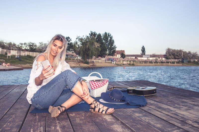 妇女坐木码头和发短信 免版税图库摄影
