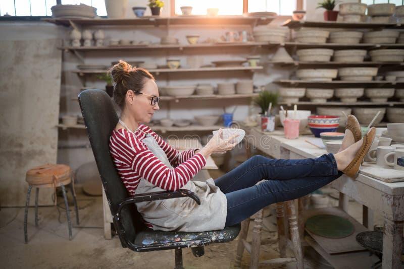 妇女坐检查碗的椅子 图库摄影