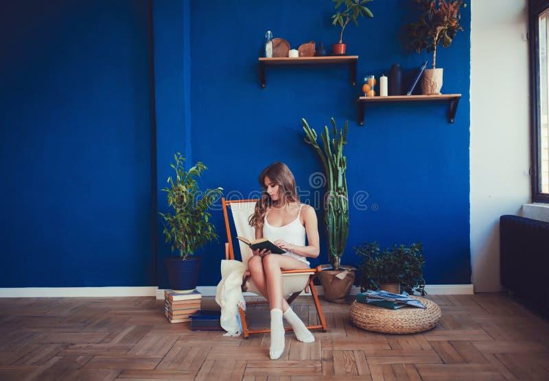 妇女坐椅子早晨,看书,卷发,在家感到舒适 免版税库存照片