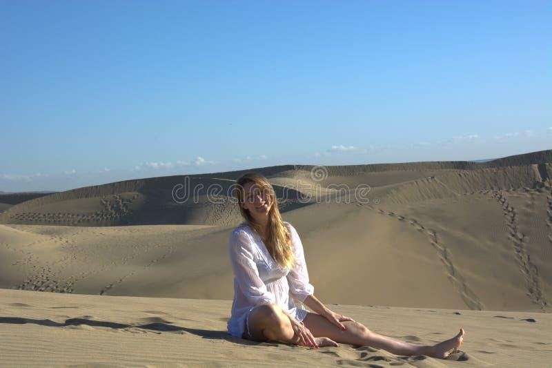 妇女坐沙丘 库存照片