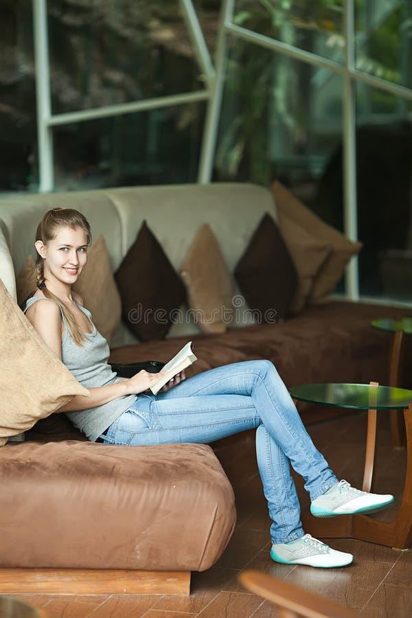 妇女坐沙发和阅读书 免版税图库摄影