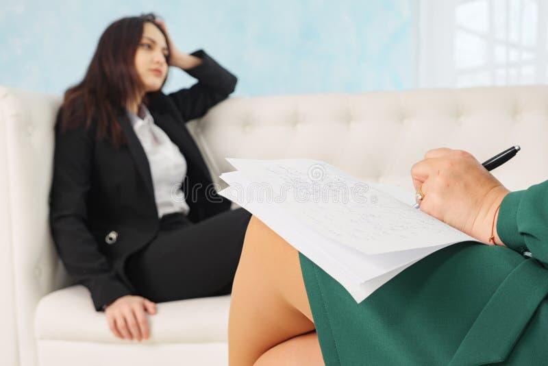 妇女坐沙发谈话与他的治疗师在疗期 图库摄影