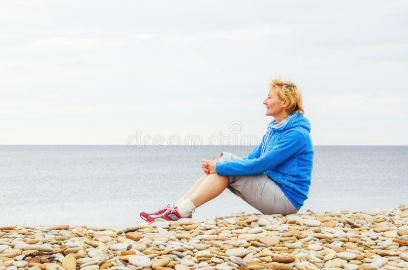 妇女坐海滩和神色入距离 免版税库存照片