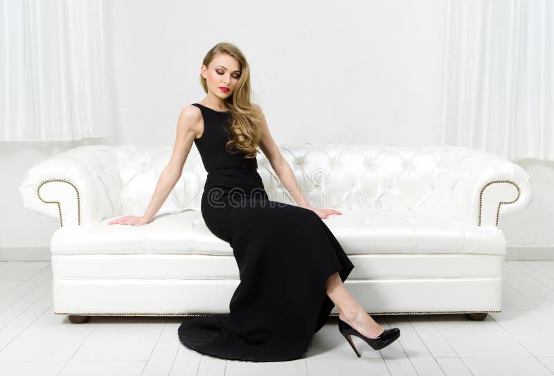 妇女坐白革沙发 免版税库存图片
