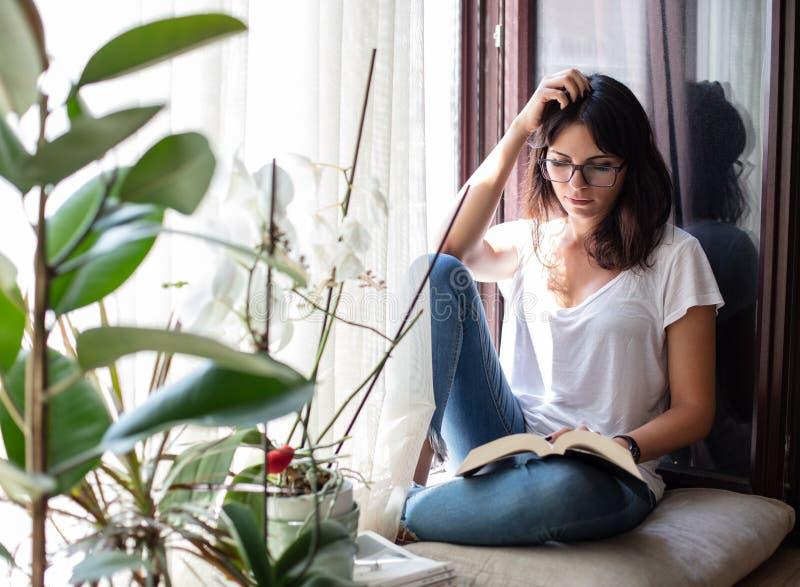 妇女坐的读书或学习在靠窗座位 免版税图库摄影