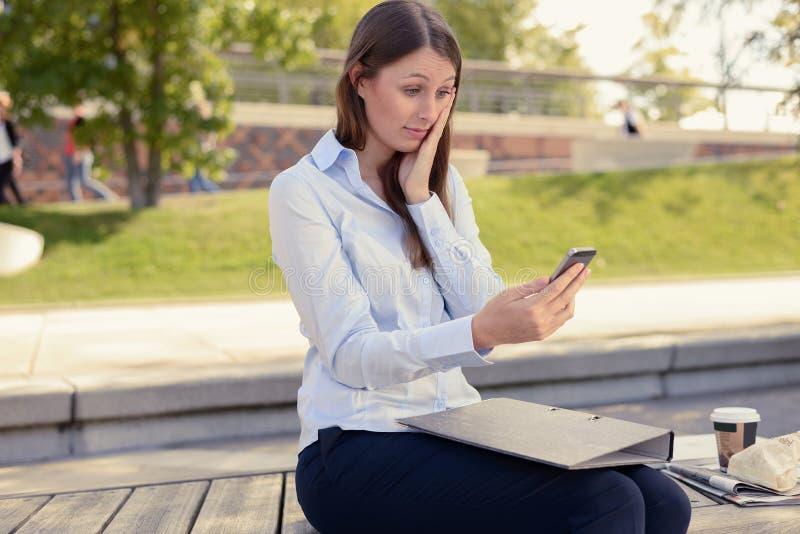 妇女坐的读与担心的神色的sms 库存图片
