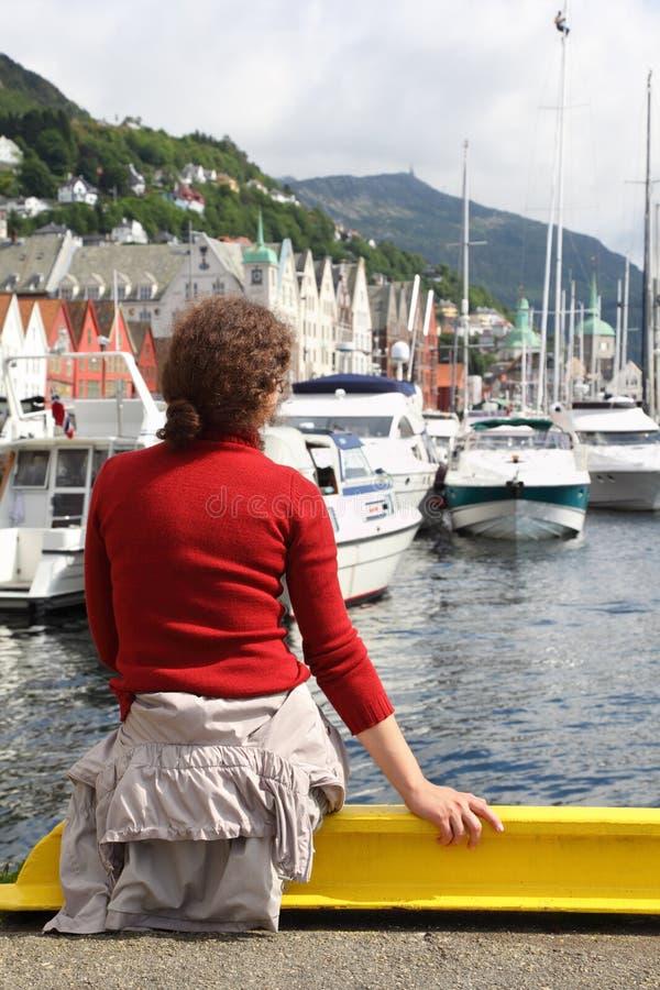 妇女坐码头在有小船的码头 图库摄影
