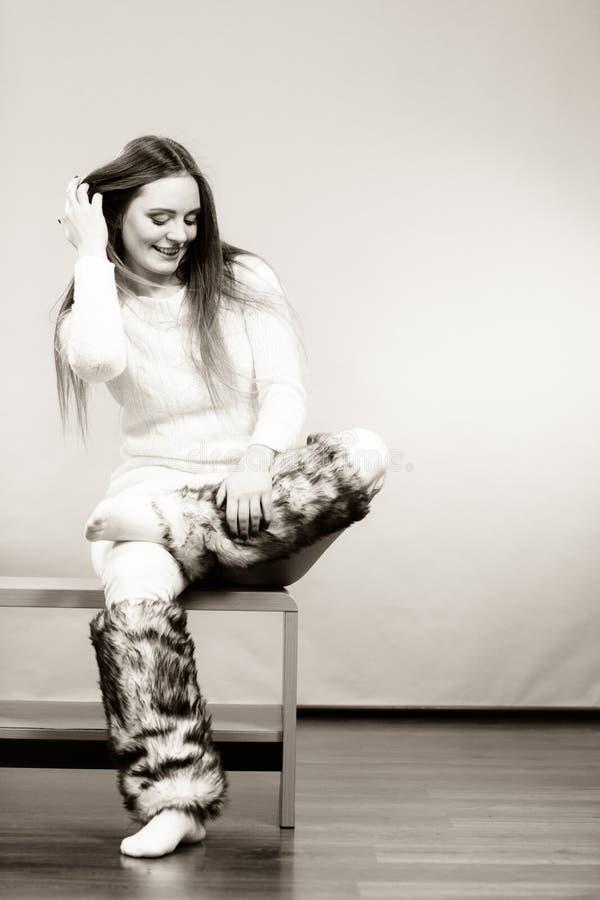 妇女坐穿毛茸的鞋子的长凳 库存图片