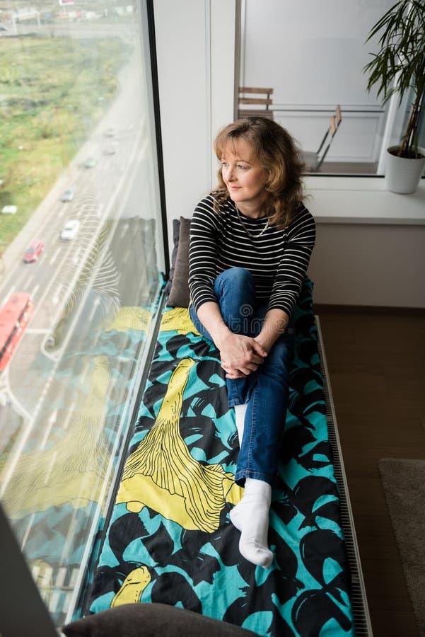 妇女坐窗口壁架床 库存照片