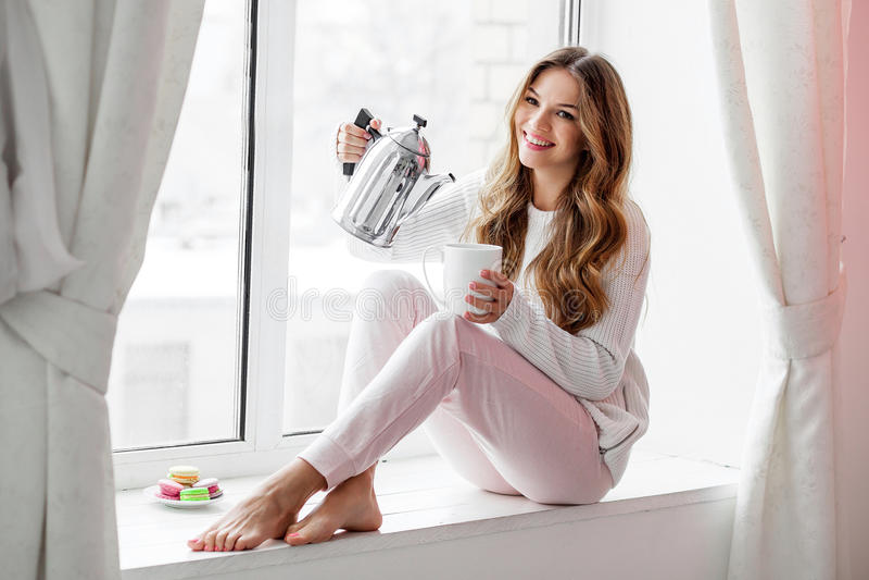 妇女坐窗台和倾吐的茶或者咖啡从水壶 库存图片