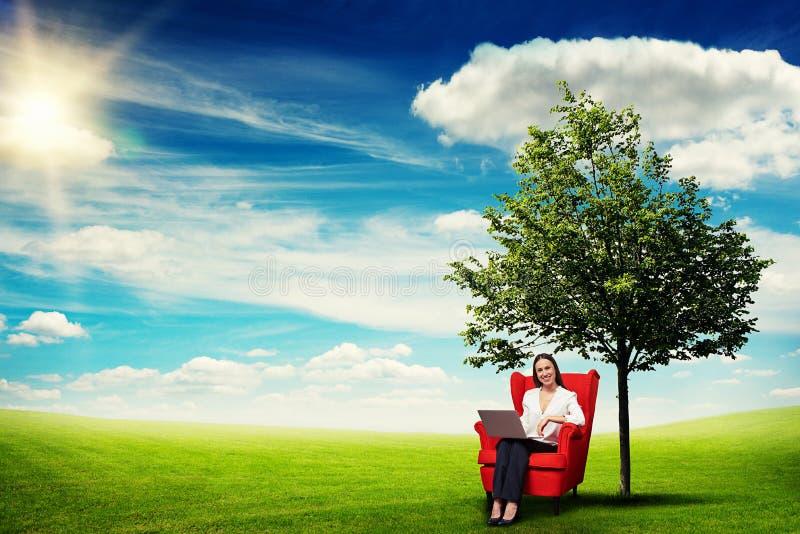 妇女坐红色椅子 库存图片