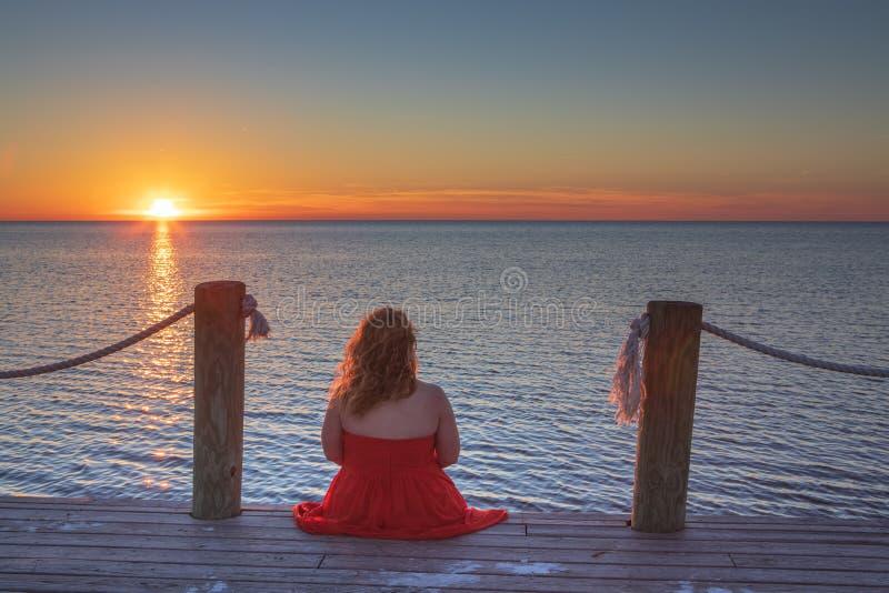 妇女坐船坞观看的日落齐射NC 库存图片