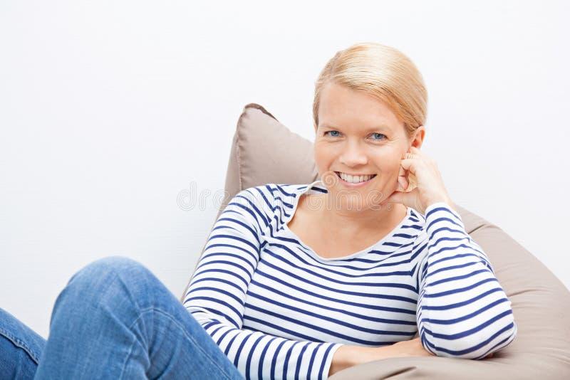 妇女坐装豆子小布袋 免版税图库摄影
