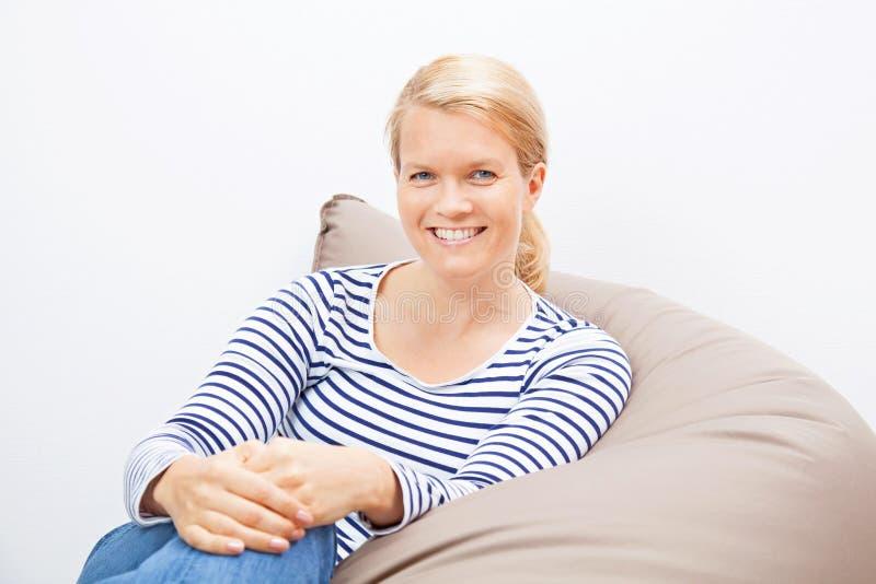 妇女坐装豆子小布袋 图库摄影
