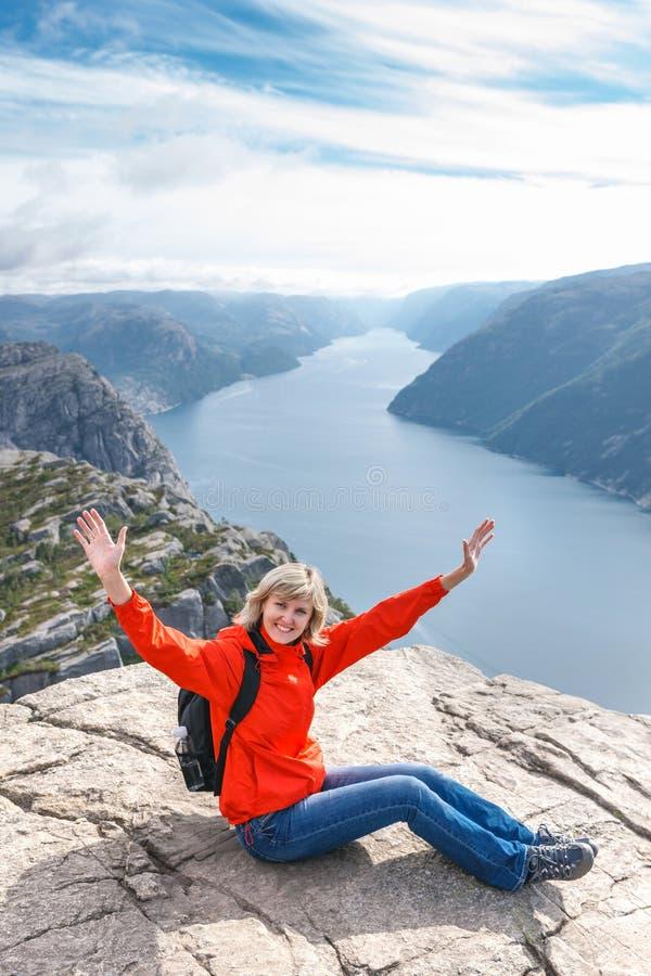 妇女坐讲坛岩石/布道台,挪威 库存照片