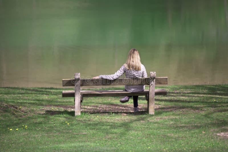 妇女坐长凳在水附近 库存图片