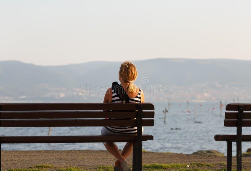 妇女坐长凳 免版税库存照片