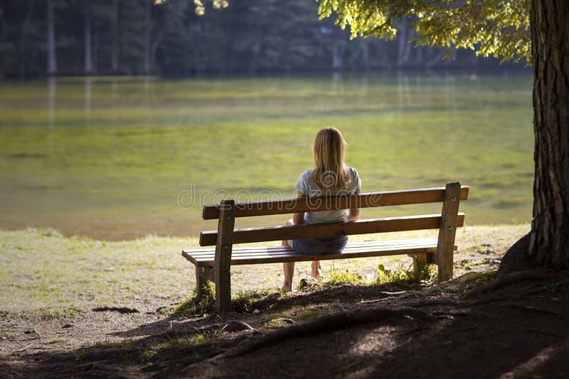 妇女坐长木凳 免版税库存照片