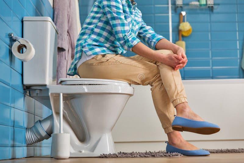 妇女坐马桶在卫生间里,底视图 免版税库存照片
