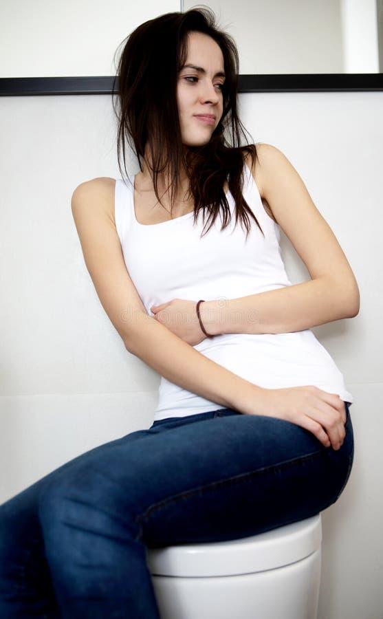 妇女坐马桶,拉腹痛 免版税库存图片
