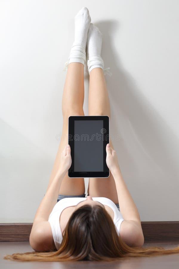 妇女坐读片剂读者的地板 图库摄影