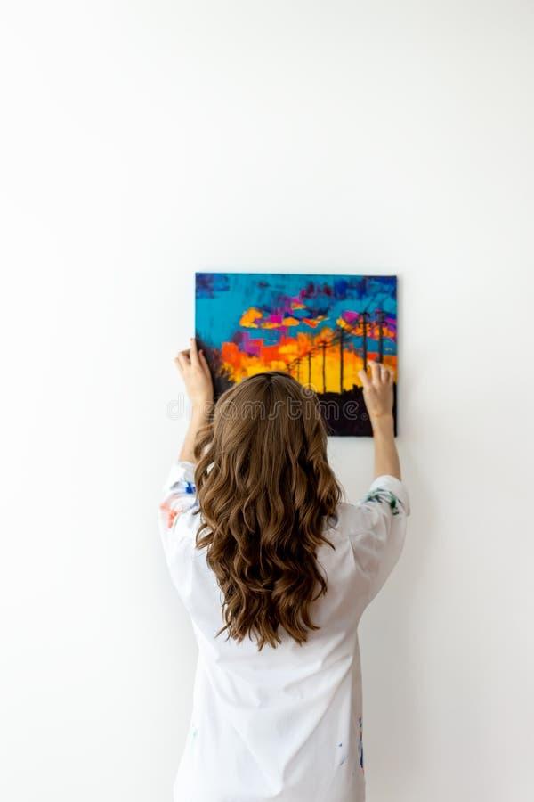 妇女垂悬的图片背面图在墙壁上的 免版税库存照片