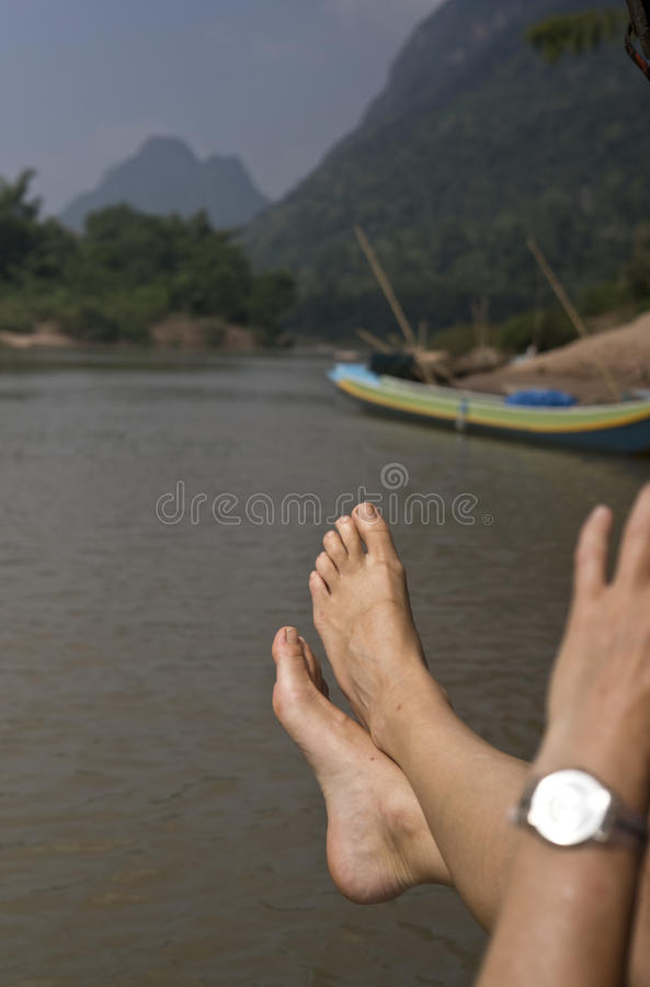 妇女垂悬脚在河的一条小船外面 免版税图库摄影