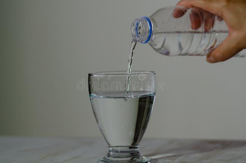 妇女填装水入玻璃 免版税库存图片