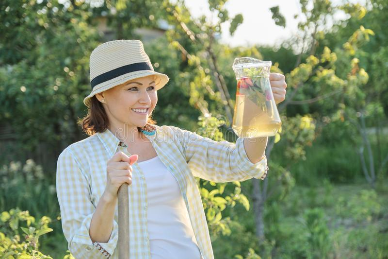 妇女夏天室外画象有由草莓薄荷的草本做的自然饮料的,妇女从事园艺 图库摄影