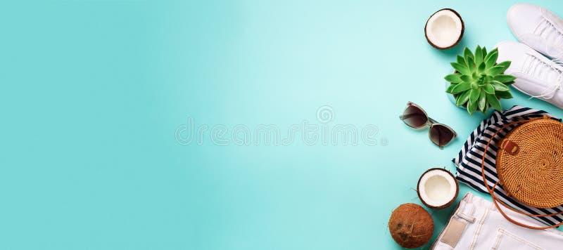妇女夏天旅行衣裳在蓝色背景移动 牛仔裤,运动鞋,竹袋子、太阳镜、椰子和多汁植物 免版税图库摄影