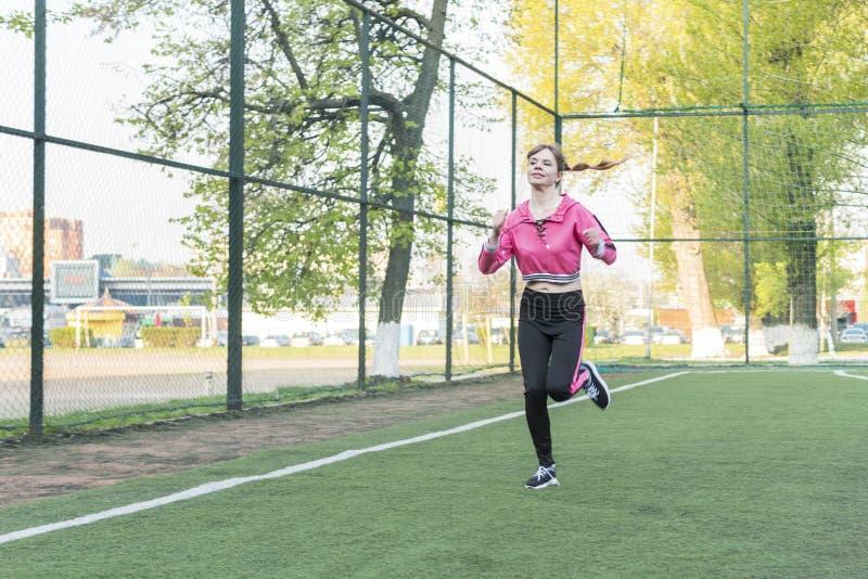 妇女奔跑通过体育场 库存图片