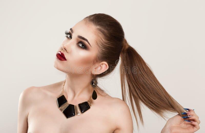 妇女女孩握她的头发,要显示她的发型褐色头发颜色 免版税图库摄影