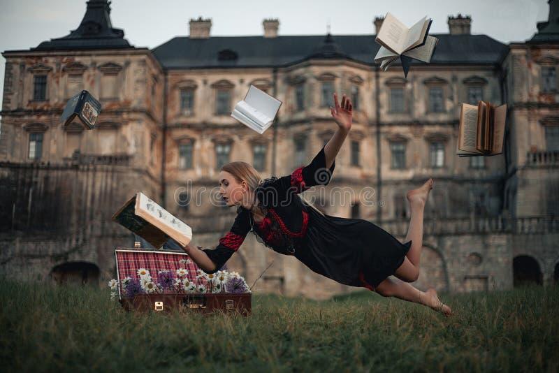 妇女女巫在空气读书并且飞行反对古老城堡背景  免版税库存照片