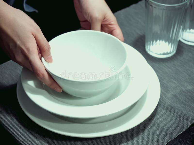 妇女女服务员举行的手和安排白色碗和盘 免版税库存照片