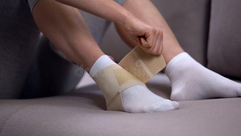妇女定象两皮带在适当的位置的脚腕套,被扭伤的联接,医疗保健 免版税库存图片