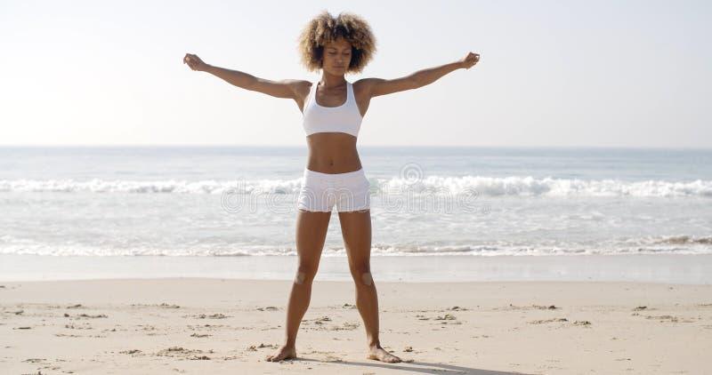 妇女实践在海滩的瑜伽 免版税库存图片