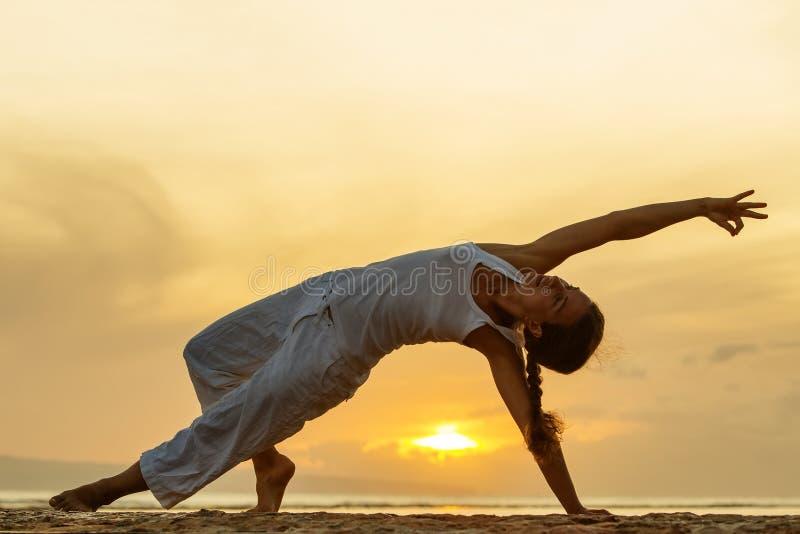 妇女实践瑜伽在海滨在巴厘岛的日落indone的 免版税库存图片