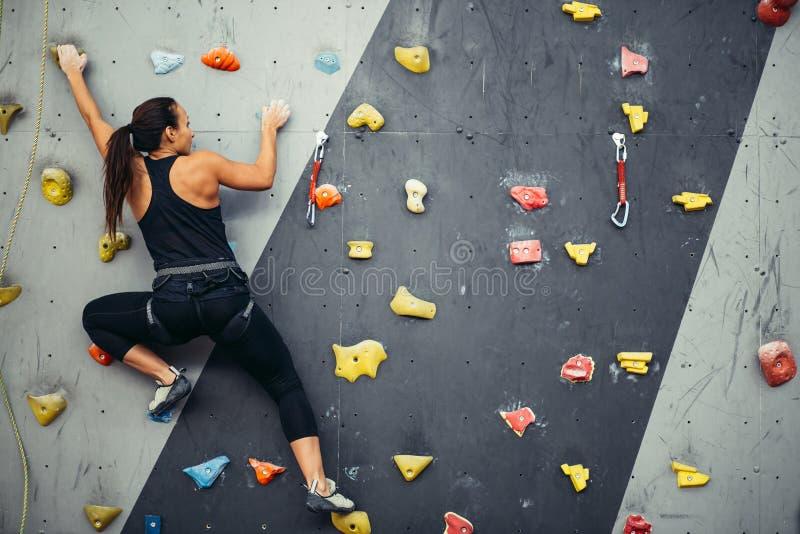 妇女实践的攀岩在人为墙壁上户内 活跃生活方式和bouldering的概念 免版税图库摄影